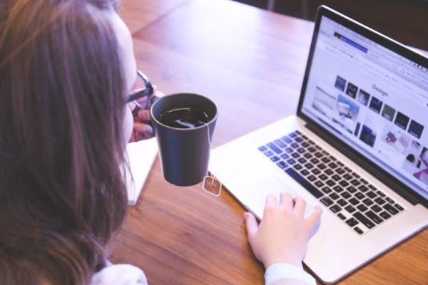 Kobieta z kawą i laptopem.